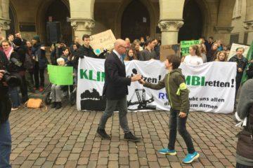 Auf dem Bild sind Jugendliche bei einer Fridays For Future Demonstration vor dem Rathaus in Münster zu sehen. Sie halten Banner und Plakate hoch. Im Vordergrund sieht man einen Jugendlichen, der dem Bürgermeister Markus Lewe ein Mikrofon reicht.