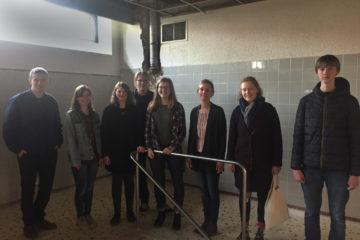 Auf dem Bild sind acht Jugendliche zu sehen. Sie stehen in einem alten Schwimmbadgebäude. Man kann Fliesen an den Wänden und den Einstieg ins ehemalige Schwimmbecken erkennen.