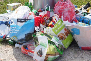 Das Bild zeigt einen Haufen verschiedener Papier- und Plastiktüten, die mit Müll gefüllt sind. Sie lehnen an einem Mülleiner am Rand eines Kiesweges. Im Hintergrund ist Rasen zu sehen.