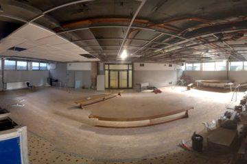 Das Bild zeigt einen großen Raum. In der Mitte stehen lange Bänke, an den Rändern des Raumes lässt sich Baumaterial erkennen. An den Wänden sind Fliesen und links im Bild ist ein Beckeneinstieg zu sehen. Daran lässt sich erkennen, dass der Raum mal ein Schwimmbad war.