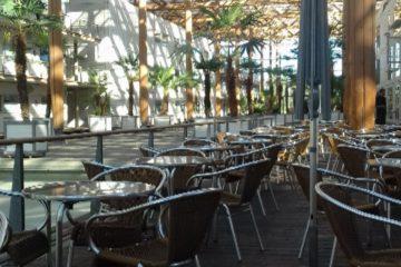 Das Bild zeigt den leeren Außenbereich eines Cafés. Kleine runde Tische mit je drei Stühlen stehen in zwei langen Reihen. Zwischen ihnen steht ein eingeklappter Sonnenschirm. Im Hintergrund sind weiße Gebäude und Palmen zu sehen. Der Bereich ist teilweise mit Holzbalken überdacht, wodurch Schatten in das Bild geworfen werden.