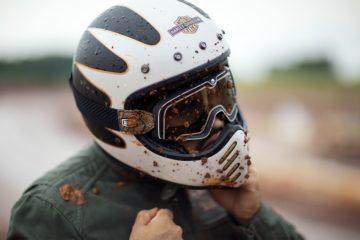Das Bild zeigt den Oberkörper eines Dirt Bike-Fahrers. Die Person trägt einen Helm und eine Schutzbrille, auf denen große Dreckspuren zu sehen sind.