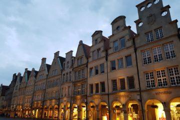 Das Bild zeigt die Fassaden vom Prinzipalmarkt in Münster. Die Eingänge sind hell erleuchtet.