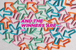 """Das Bild zeigt Büroklammern in Form von Pfeilen. Die Klammern haben bunte Farben und zeigen in verschiedene Richtungen. In der Mitte ist ein Schriftzug mit den Worten """"And the winners are..."""" zu sehen."""