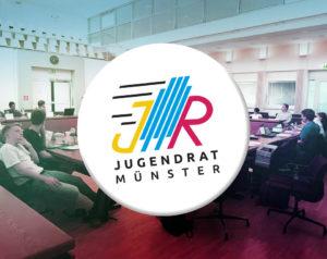 Auf dem Bild ist im Hintergrund eine Sitzung des Jugendrates abgebildet. Es sind Jugendliche an Tischen zu sehen. Im Vordergrund steht das Logo des Jugendrats. Auf dem Logo sind die Buchstaben J und R in gelb und rot zu sehen. In der Mitte ist in blau das Rathausgebäude angedeutet.