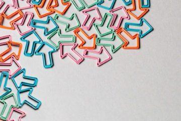 Das Bild zeigt Büroklammern in Form von Pfeilen. Die Klammern haben bunte Farben und zeigen in verschiedene Richtungen.